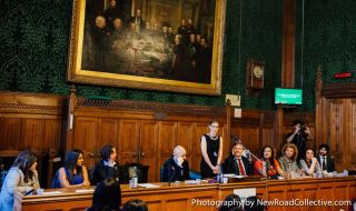 A woman standing up to present in a panelled room with other people sitting down.