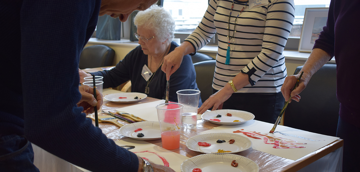 Group around table making artwork for Picturing Parkinsons